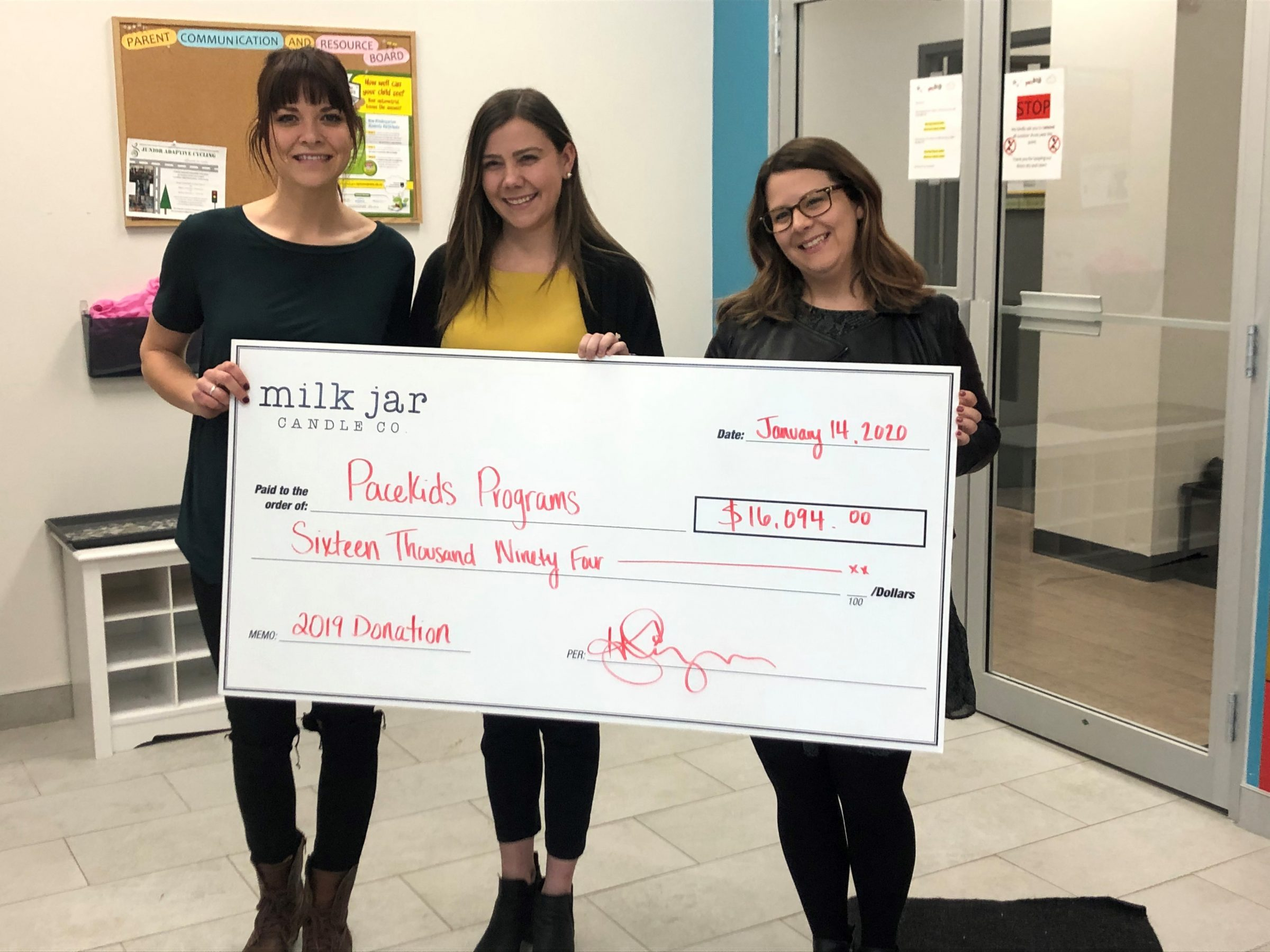 Milk Jar Candle Co & Pacekids Employees hold cheque for special needs program donation