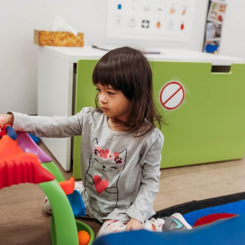 Little girl with special needs playing with toy