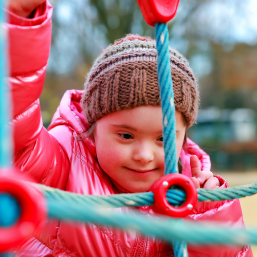 Special Needs Child Playing on Playground, Down Syndrome